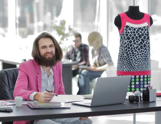 Lo stilista usa una tavoletta grafica seduto a una scrivania in studio.