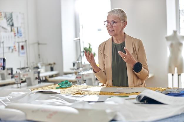 Stilista di moda con occhiali e cuscino a spillo nel polso gira video in laboratorio di luce
