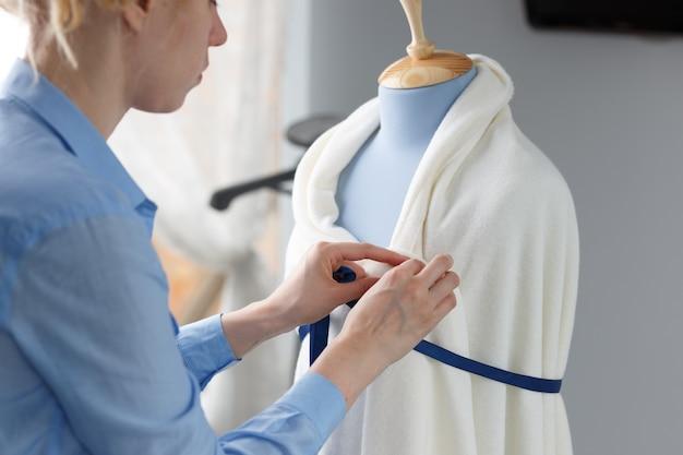 Stilista che lavora con un manichino sarto blu nel suo laboratorio.