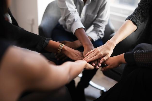 Stilisti che fanno una pila di mani durante una riunione