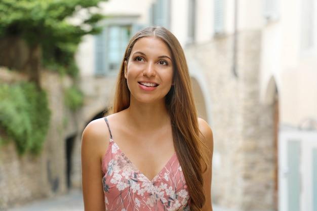Moda donna vestita che cammina per le strade di una piccola città medievale italiana.