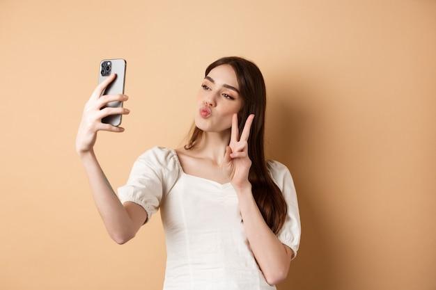 Fashion blogger femminile arriccia le labbra e mostra il segno v sulla fotocamera dello smartphone, prendendo selfie per i social media, in piedi sul beige.