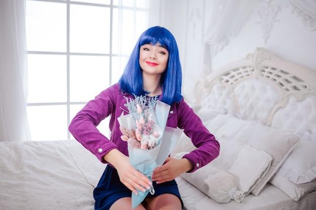 Maniaco della moda. ragazza sintetica sorridente glamour, bambola finta con i capelli blu tiene in mano il mazzo di fiori mentre è seduta sul letto bianco.