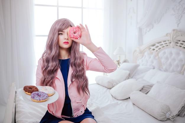 Maniaco della moda. ragazza sintetica glamour, bambola finta con sguardo vuoto e lunghi capelli lilla tiene in mano una ciambella rosa davanti al viso mentre è seduta nella camera da letto bianca. elegante bella donna in abito blu