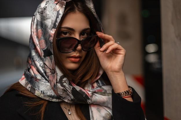 Moda ritratto fresco giovane donna attraente in una sciarpa di seta elegante alla moda sulla testa con labbra sexy. la ragazza moderna raddrizza gli occhiali da sole alla moda e guarda la telecamera. bella signora d'affari.