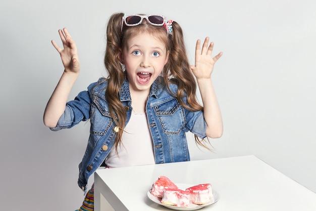 Moda divertente ragazza dai capelli rossi con trecce e occhiali in testa vuole mangiare una torta, un'espressione facciale felice. foto dello studio su sfondo di colore chiaro. compleanno, vacanza