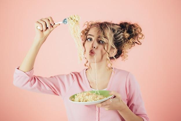 Ragazza di moda che mangia le tagliatelle. piatto di spaghetti della stretta della ragazza. colazione mattutina. donna attraente che mangia tagliatella. adorabile donna con i capelli ricci che mangia pasta. moda e bellezza. dieta, cibo, pasto, italia.