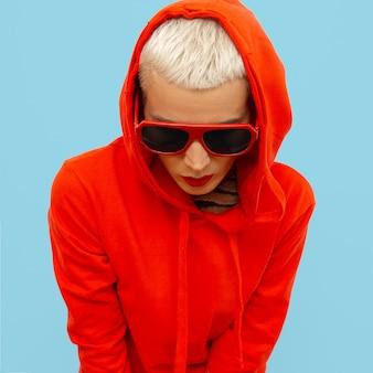 Ragazza alla moda in felpa rossa con cappuccio e occhiali da sole street urban style