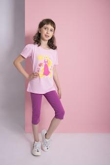 Ragazza di modo in vestiti alla moda sul fondo colorato della parete. vestiti luminosi autunnali sui bambini, un bambino in posa su uno sfondo rosa viola colorato. russia, sverdlovsk, 6 aprile 2019