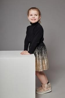 Adatti la ragazza con capelli lunghi in abbigliamento casual che si siede su un cubo bianco e su una posa.