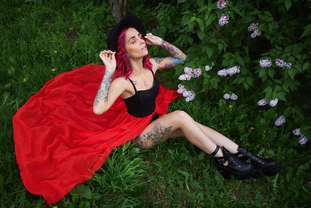 Moda ragazza con capelli rossi e grande cappello, ritratto primaverile in colori lilla in estate. bellissimo vestito rosa rosso, tatuaggi sul corpo di una donna. trucco luminoso, colorazione professionale dei capelli