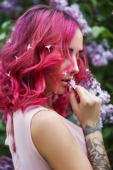 Ragazza alla moda con i capelli rossi e la vocazione del grande cappello, ritratto primaverile nei colori lilla in estate. bellissimo vestito rosa rosso, tatuaggi sul corpo di una donna. trucco luminoso, colorazione professionale dei capelli