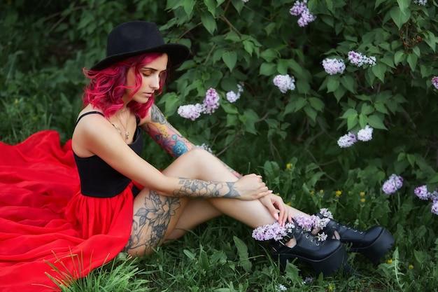 Moda ragazza con vocazione capelli rossi, ritratto primaverile nei colori lilla in estate. bellissimo vestito rosa rosso, tatuaggi sul corpo di una donna
