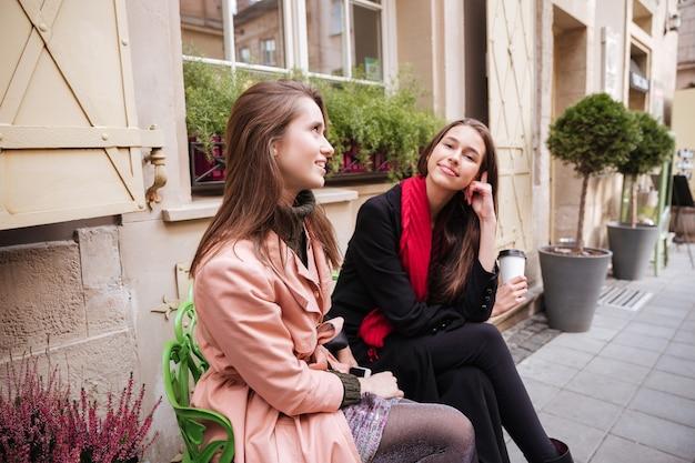 Le ragazze alla moda con i cappotti sono sedute per strada