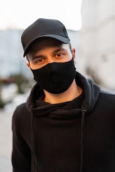 Uomo bello alla moda con berretto nero e maschera medica con felpa con cappuccio alla moda per strada. concetto di stile casual maschile pandemico e urbano