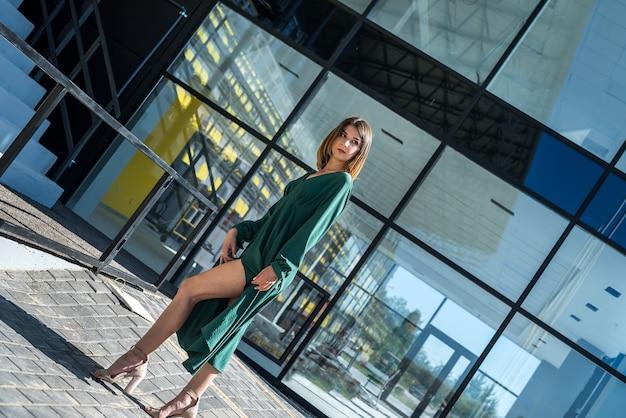 Moda e donna felice in abito verde in piedi contro la moderna architettura di vetro intorno alla città