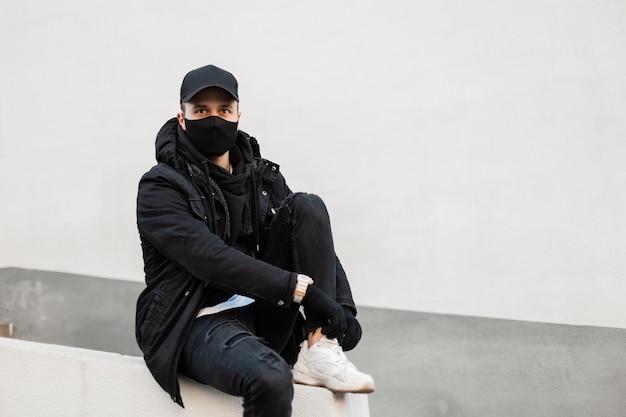 L'uomo hipster alla moda con una maschera protettiva e un berretto nero in una giacca elegante e una felpa con cappuccio alla moda con scarpe da ginnastica si siede per strada e si allaccia i lacci delle scarpe.