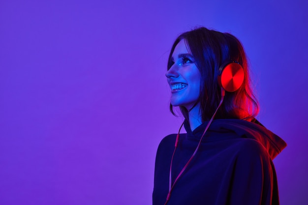 La donna di moda hipster sorride e indossa le cuffie per ascoltare musica su sfondo al neon di colore in studio.