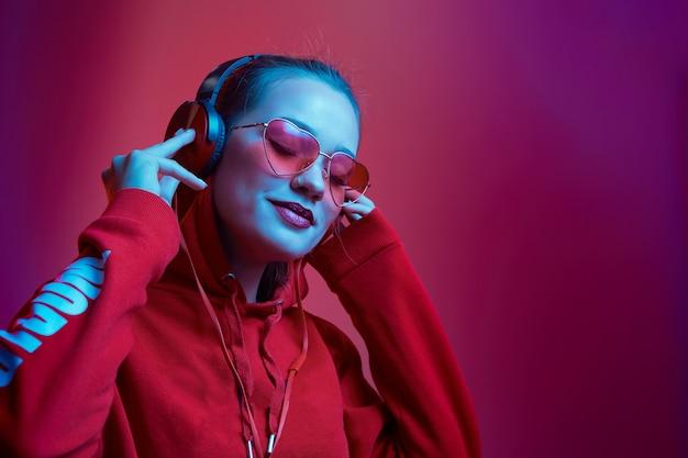 La donna di moda hipster indossa occhiali alla moda e cuffie che ascoltano musica su sfondo al neon di colore in studio.