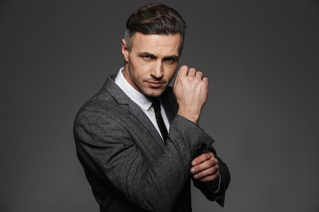 Adatti l'immagine dell'uomo che indossa lo sguardo del vestito, mentre fissano il gemello o il bottone sulla manica della giacca, isolata sopra la parete grigia