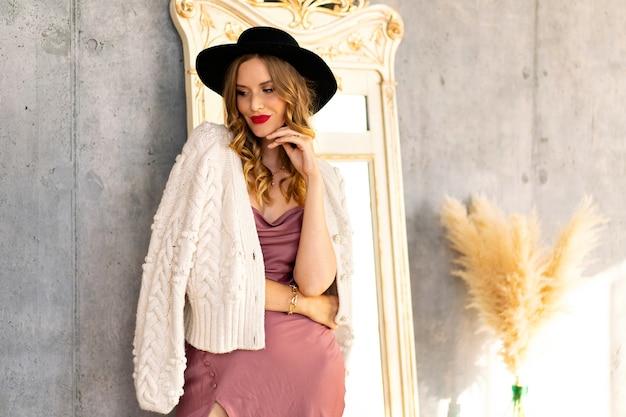 Moda ritratto indoor di bella donna glamour in posa vicino al muro grigio in una giornata di sole, indossando un abito di seta, un caldo cardigan lavorato a maglia e un cappello nero