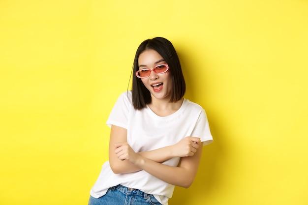 Concetto di moda e stile di vita. donna asiatica impertinente e sicura di sé in occhiali da sole alla moda che guarda sicura di sé alla telecamera, in piedi su sfondo giallo.