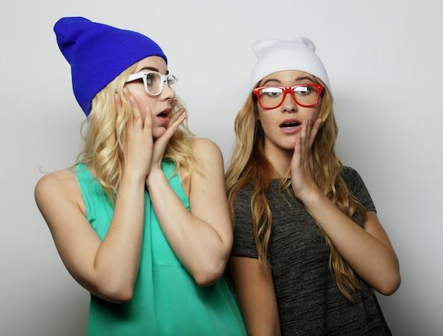Ritratto di stile di vita di moda di due migliori amiche di ragazze giovani hipster, con trucco luminoso e cappelli alla moda simili, facendo facce buffe.