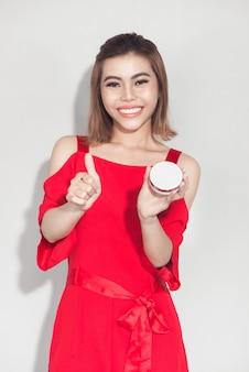 Ritratto di stile di vita alla moda di una giovane donna asiatica che tiene in mano un prodotto cosmetico di base