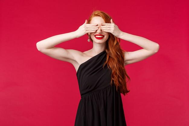 Concetto di moda, lusso e bellezza. ritratto di giovane donna splendida elegante con capelli lunghi rossi, vestito lussuoso nero, occhi coperti con gli occhi bendati contando dieci per vedere sorpresa, sorridente, muro rosso