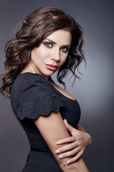 Ritratto del primo piano della donna di bellezza di lusso di modo. bruna con i capelli ricci. pelle del viso perfetta, bel trucco, cura della pelle