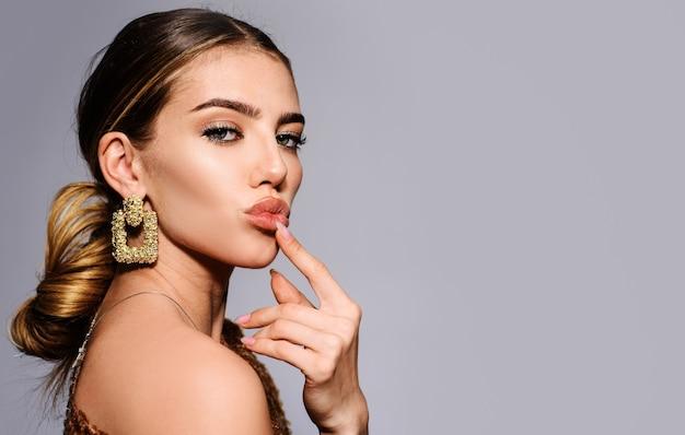 Trucco e cosmetici alla moda, bella donna con gioielli, accessori alla moda, tendenze di bellezza.