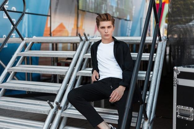 Modello di moda uomo in vestiti alla moda si siede sulla strada