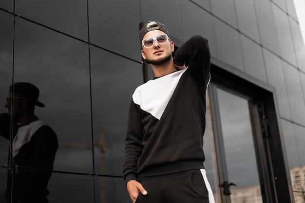 Uomo di moda con occhiali da sole e berretto in felpa cammina in città