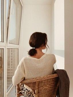Moda e concetto minimo. una giovane donna con i capelli scuri, un caldo maglione bianco, una gonna con stampe animalier sdraiata su una sedia di paglia a guardare il tramonto