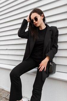Modello di moda attraente giovane donna in eleganti occhiali da sole in vestiti neri alla moda della nuova collezione estiva alla moda sta riposando vicino all'edificio in legno grigio vintage in città. bella ragazza all'aperto.