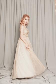 Modello di moda in bellissimo abito di chiffon fluente beige di lusso, donna in abito da sera lungo volante con un abito, modello fantastico di fantasia. tessuto di seta che ondeggia sul vento. tessuto di raso che scorre, onde di un vestito