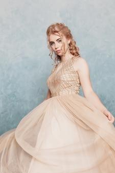 Modello di moda in bellissimo abito di chiffon fluente beige di lusso, donna in abito da sera lungo volante con un abito, modello fantasy sbalorditivo. tessuto di seta che ondeggia sul vento. tessuto di raso che scorre, onde di un vestito