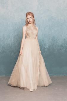Modella in bellissimo abito di chiffon fluente beige di lusso