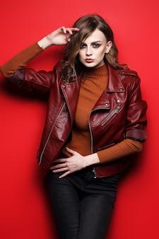 Modello di moda bella giovane donna. giacca di pelle, girato in studio, sfondo rosso