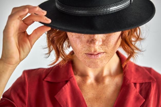 Modello di moda in cappello nero, guardando in basso chiudendo gli occhi, ritratto in studio