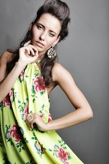 Modello di moda in abito luminoso su sfondo grigio