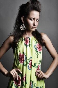 Modello di moda in abito luminoso sul muro grigio