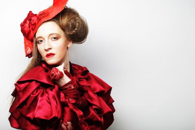 Modella in costume rosso brillante e cappello rosso. colpo dello studio.