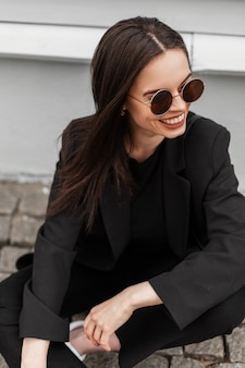 Modello di moda allegra giovane donna con un sorriso carino in eleganti occhiali da sole in vestiti neri alla moda della nuova collezione alla moda giovanile sta riposando vicino all'edificio in legno in città. la ragazza felice si siede all'aperto.