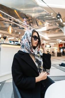 Moda modello affari europei giovane donna alla moda con sciarpa di seta vintage sulla testa in occhiali da sole sta riposando nella caffetteria. la ragazza elegante alla moda si rilassa nel negozio moderno. bella signora alla moda.