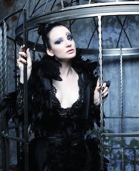 Modello di moda in abito fantasia in posa in gabbia d'acciaio.