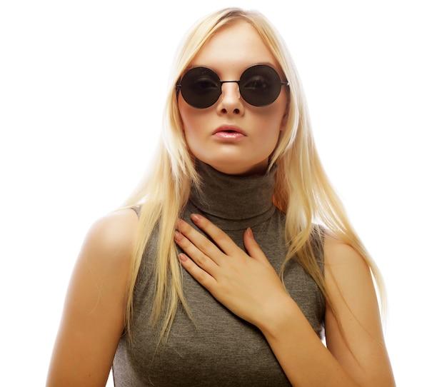 Ragazza del modello di moda isolata sopra la parete bianca. donna bionda alla moda di bellezza che posa in vestiti alla moda e grandi occhiali da sole.