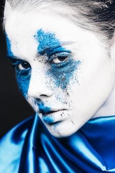 Ritratto di ragazza modella con trucco colorato in polvere