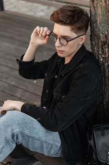 Modello di moda bel giovane in abiti alla moda in denim raddrizza occhiali vintage all'aperto