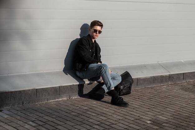 Modello di moda bel giovane con acconciatura alla moda in occhiali da sole in giacca di jeans nera